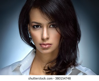 Portrait of a beautiful, fashion, sexy brunette woman with full lips and perfect hair and skin. In white shirt. Looks into the camera