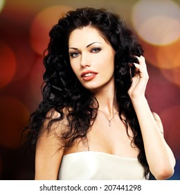 Portrait of the  beautiful fashion sexy  woman with long curly hairstyle poses indoor
