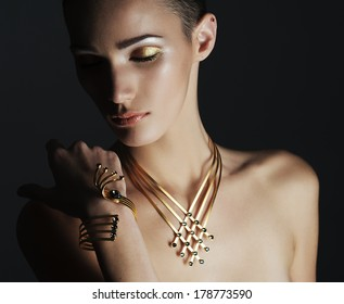 portrait of the beautiful fashion woman with black and gold makeup. Gold jewerly. expensive and luxurious