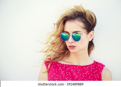 Portrait of Beautiful Fashion Woman in Sunglasses. Trendy Romantic Girl in Summer. Stylish Lovely Female. White Wall Background with Copy Space. Not Isolated Toned Photo.