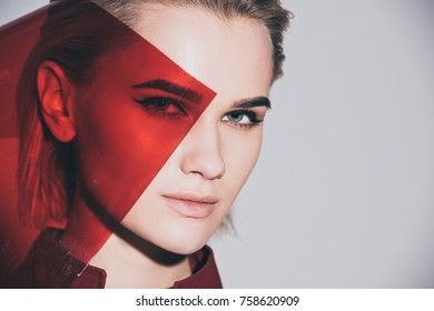 portrait of beautiful fashionable girl posing with red filter, isolated on grey