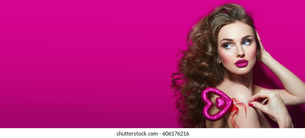 Portrait of a beautiful fashionable girl with smooth skin on a pink background with a shiny