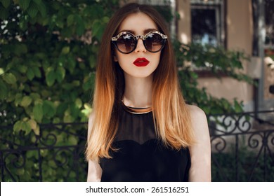 Portrait of a beautiful and fashionable girl in sunglasses with a gold rim. Posing in the park with professional hair style and make up. Blond hair with ombre coloring