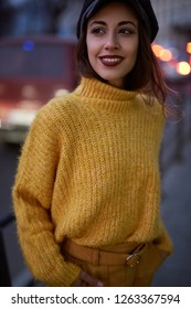 portrait of a beautiful fashionable stylish woman in bright yellow sweater and skirt walking and posing outdoors at evening, street style shooting