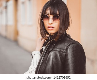 Portrait of beautiful fashionable woman walking and posing outdoors. Cool attitude.