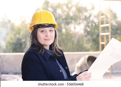 Portrait of a beautiful female architect at a construction site with blueprints. Outdoors.
