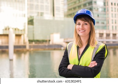 Portrait of beautiful female architect who stands idly and smiles against the background of the river and buildings, outdoors