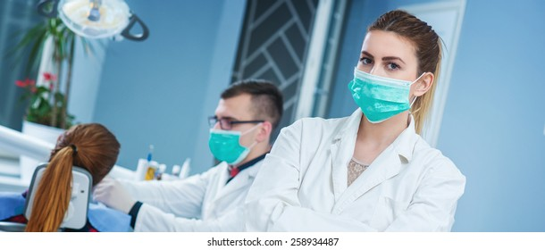 Portrait of beautiful female assistant at dentist office, doctor working with patient in background on dentist chair.