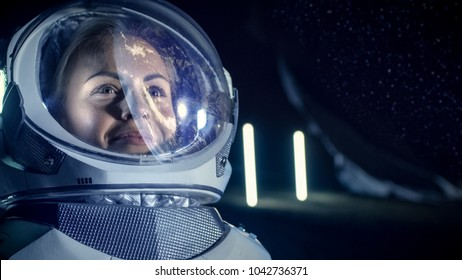 Portrait of the Beautiful Female Astronaut on the Alien Planet. Earth Reflection on her Helmet. In the Background Living Habitat. Space Travel, Exploration and Solar System Colonization Concept.
