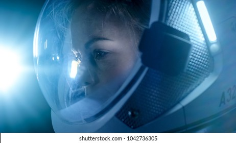 Portrait of the Beautiful Female Astronaut Space Walking, Looking around in Wonder, Space Station Illuminates Her Face. Space Travel, Exploration and Solar System Colonization Concept.