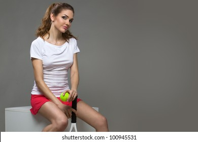 portrait of a beautiful female athletes with a tennis racket and the tennis ball in her hands