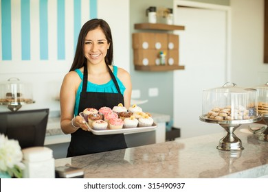 Portrait of a beautiful female business owner showing some of her freshly baked cupcakes and smiling