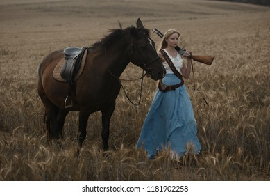 Portrait of a beautiful female cowgirl with shotgun from wild west riding a horse in the outback