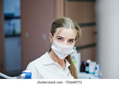 Portrait of a beautiful female dentist in a well-equipped cabinet.
