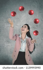 Portrait of a beautiful female entrepreneur looks happy while juggling red balls