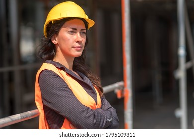 Portrait of a beautiful female factory worker wearing a protective helmet and a safety vest posing outdoors with crossed arms