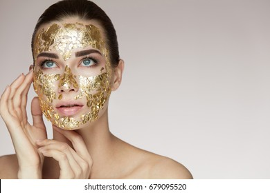 Portrait Of Beautiful Female Holding Hands Near Head And Golden Mask On Face Skin.