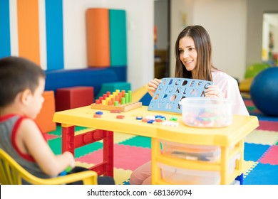 Portrait of a beautiful female language therapist working and practicing the alphabet with a kid