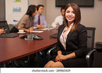Portrait of a beautiful female lawyer sitting in a conference room with a group of co-workers