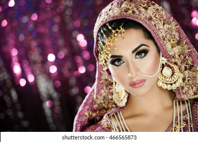 Portrait of a beautiful female model in ethnic Indian Pakistani bridal costume with heavy makeup and jewellery in landscape orientation