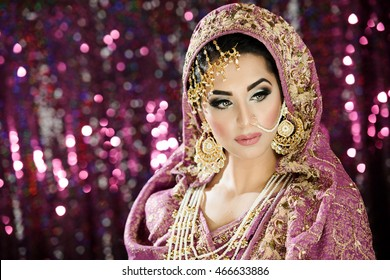 Portrait of a beautiful female model in ethnic Asian style bride costume with heavy jewellery and makeup