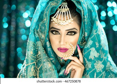 Portrait of a beautiful female model in exotic looking outfit with headdress and makeup with heavy jewellery