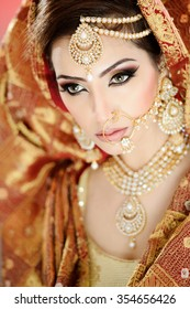 Portrait of a beautiful female model as an indian bride wearing traditional bridal costume and heavy jewellery and makeup
