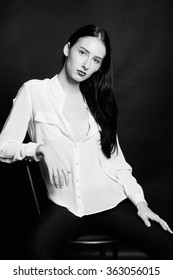 portrait of beautiful female model with perfect skin and long dark hair. Wearing casual white shirt see through. Black and white. Fashion beauty photo shoot