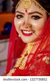 Portrait of a beautiful female model in traditional ethnic Indian Bengali bride costume with heavy jewellery and makeup