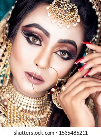 Portrait of a beautiful female model in traditional Indian bride outfit with makeup and jewellery, Looking at camera