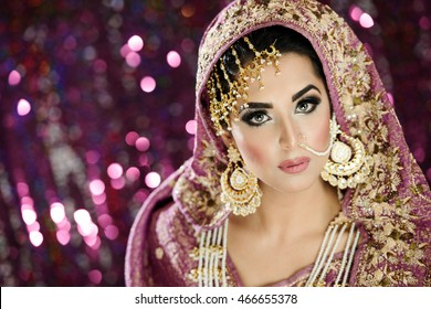 Portrait of a beautiful female model in traditional Indian bride costume with heavy jewellery and makeup in landscape orientation