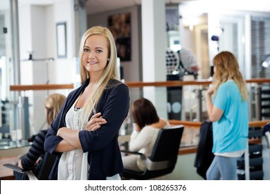 Portrait of beautiful female owner of parlor standing arms crossed with customers in background