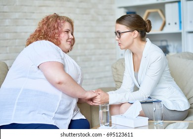 Portrait of beautiful female psychiatrist  offering psychological support to obese young woman holding hands and comforting her during therapy session on mental issues in doctors office.