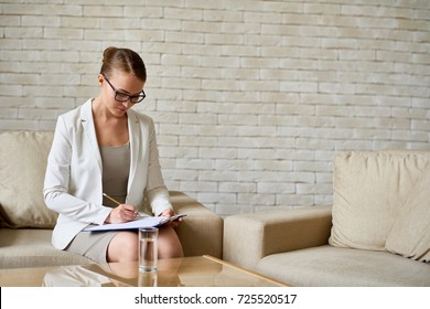 Portrait of beautiful female psychologist wearing glasses writing on  clipboard  in therapy office