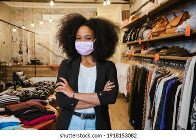 Portrait of a beautiful female sales assistant at the entrance of the business with her arms folded - Self-confident millennial owner starts a new business during the Coronavirus Covid-19 pandemic