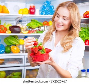 Portrait of a beautiful female standing near open fridge full of fruits and vegetables, eating fresh red ripe juicy strawberries, enjoying healthy nutrition, wellness and healthy living