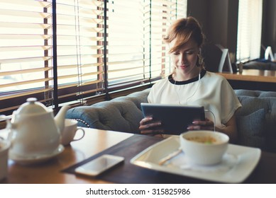 Portrait of beautiful female student listen or studying on-line training course in headphones while using her digital tablet charming young woman have video conversation while breakfast in coffee shop