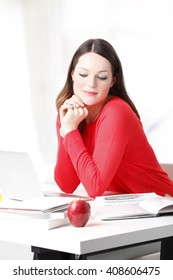 Portrait of beautiful female student sitting at desk working on her presentation at home.