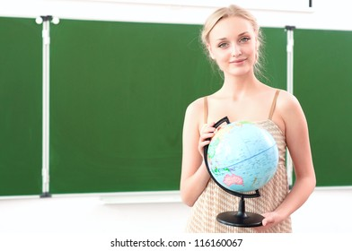 portrait of a beautiful female teacher with a globe