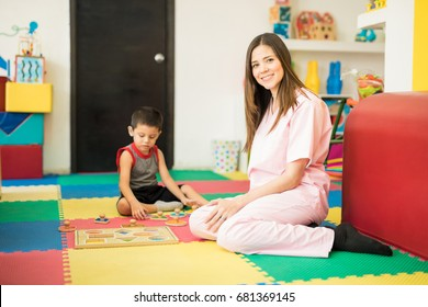 Portrait of a beautiful female therapist playing and exploring different shapes with a little boy