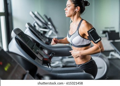 Portrait of beautiful  fit brunette woman exercising on treadmill in gym listening to music using shoulder smartphone holder
