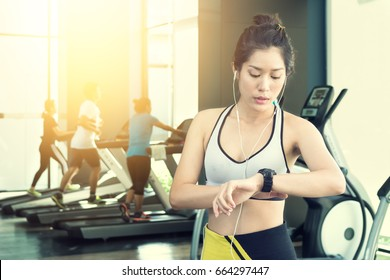 Portrait of beautiful fitness asian woman listening music and looking on wrist watch for checking time at the fitness gym.