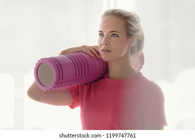 Portrait of beautiful fitness woman holding foam roller
