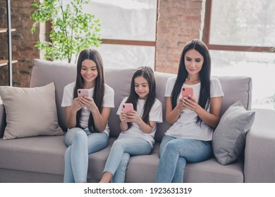 Portrait of beautiful focused addicted girls sitting on divan using device chatting browsing at house flat apartment indoors
