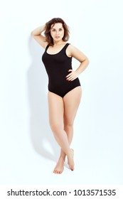 Portrait of a beautiful full-length girl in a black swimsuit on a white background.