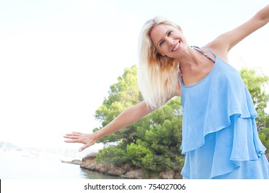 Portrait of beautiful fun tourist woman on summer holiday destination beach, joy smiling with open arms looking at camera, sea nature exterior. Middle age female enjoying travel lifestyle, freedom.