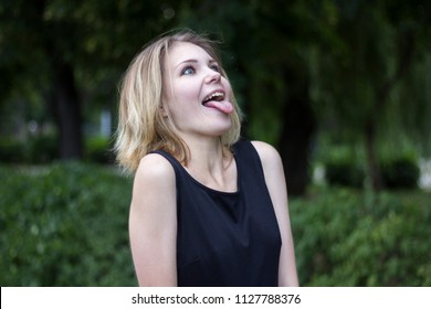 Portrait of a beautiful funny cute blond girl, wide-open mouth and sticking out her tongue, fooling around, outdoors in the park against the background of green foliage