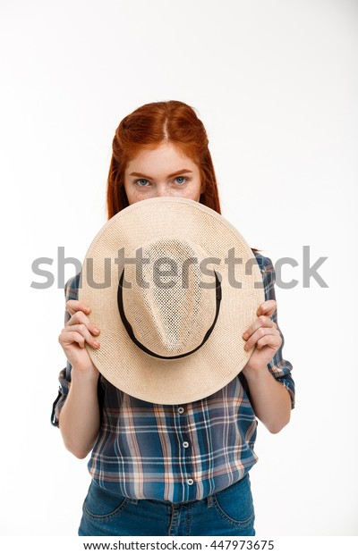Portrait of beautiful ginger girl with hat over white background.