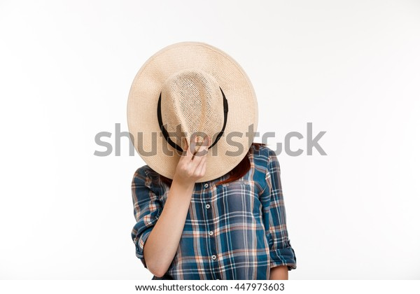 Portrait of beautiful ginger girl hiding her face with hat over white background.