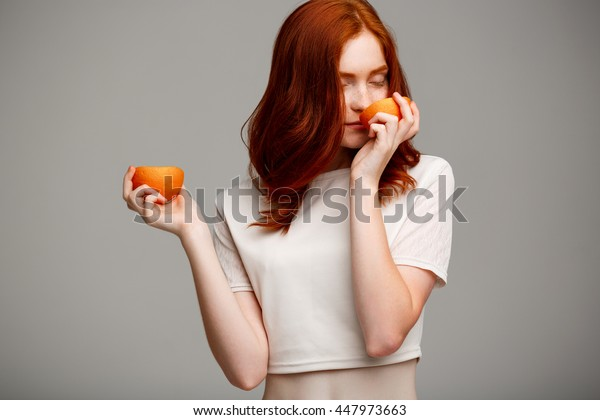 Portrait of beautiful ginger girl holding oranges over gray background.